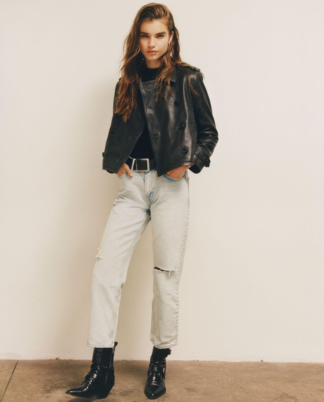 Portrait of a woman wearing a dark leather biker jacket over a black t-shirt.