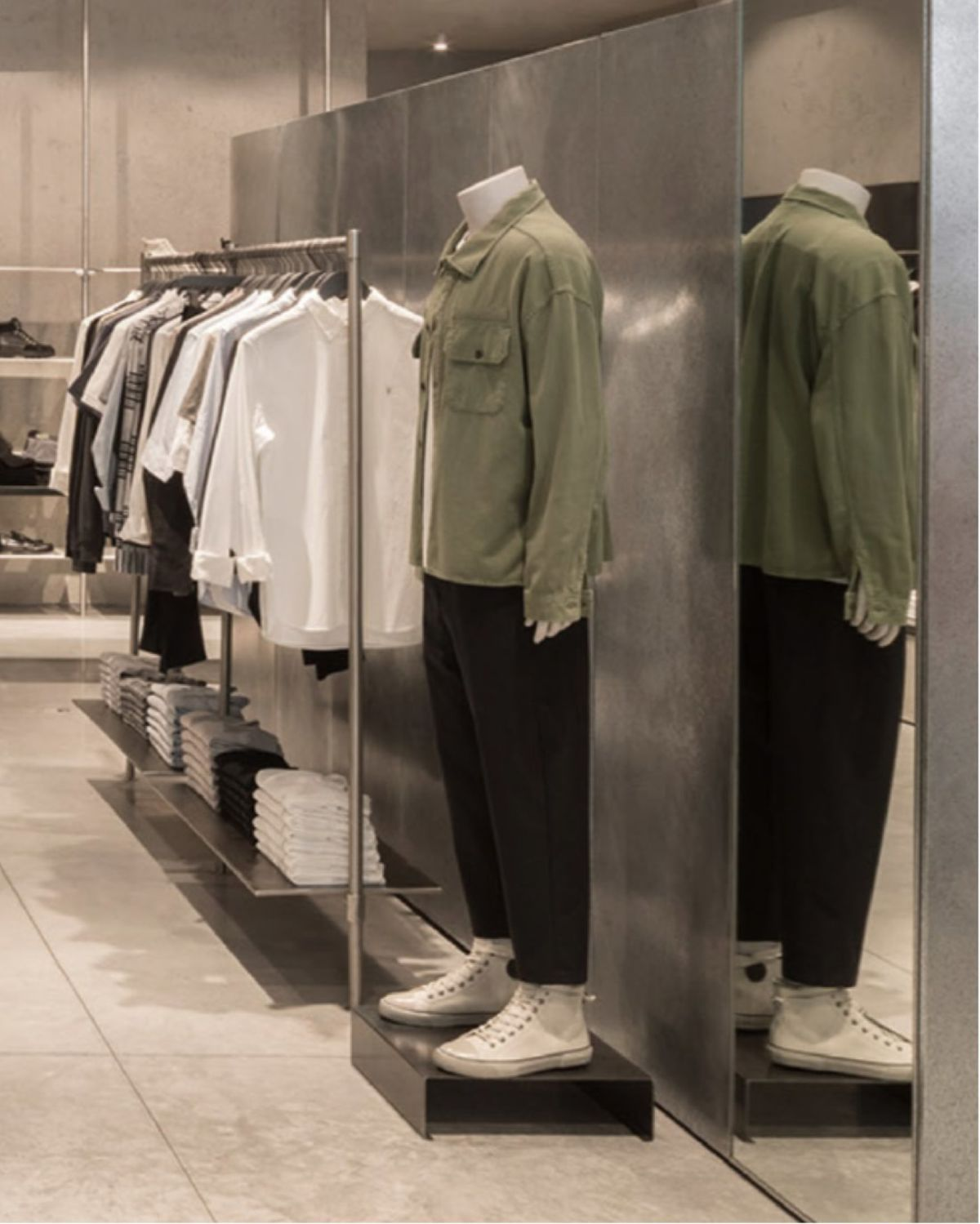 Mannequin in store near items from the men's collection.