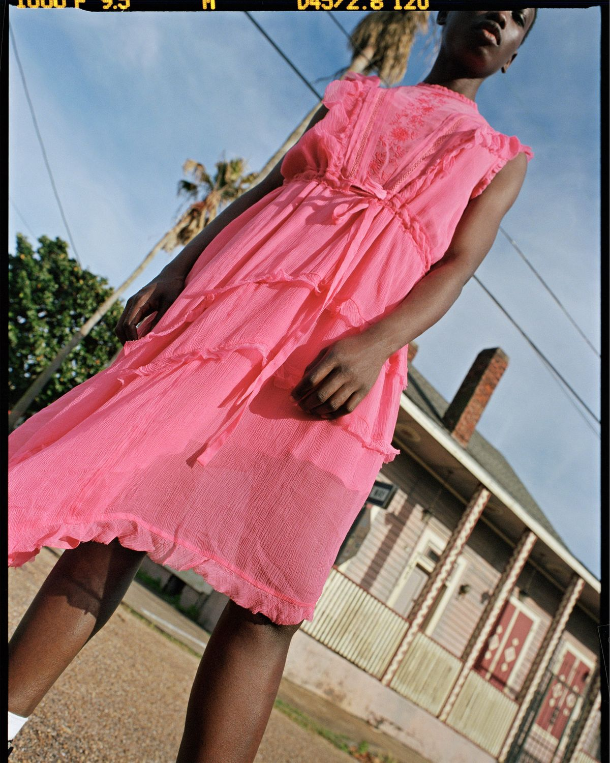 Photograph shot in the streets of New Orleans, featuring a young woman wearing a vibrant, frilled pink dress from our latest summer collection.