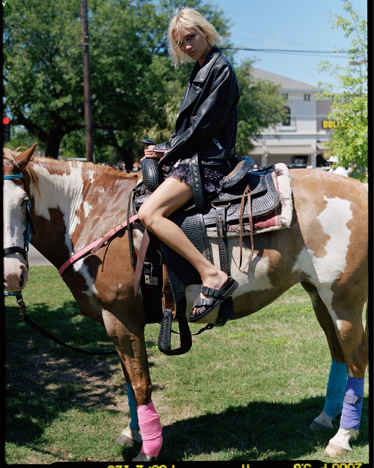 Photograph of a young woman sat on a horse wearing a black leather jacket and shorts from our most recent summer collection.