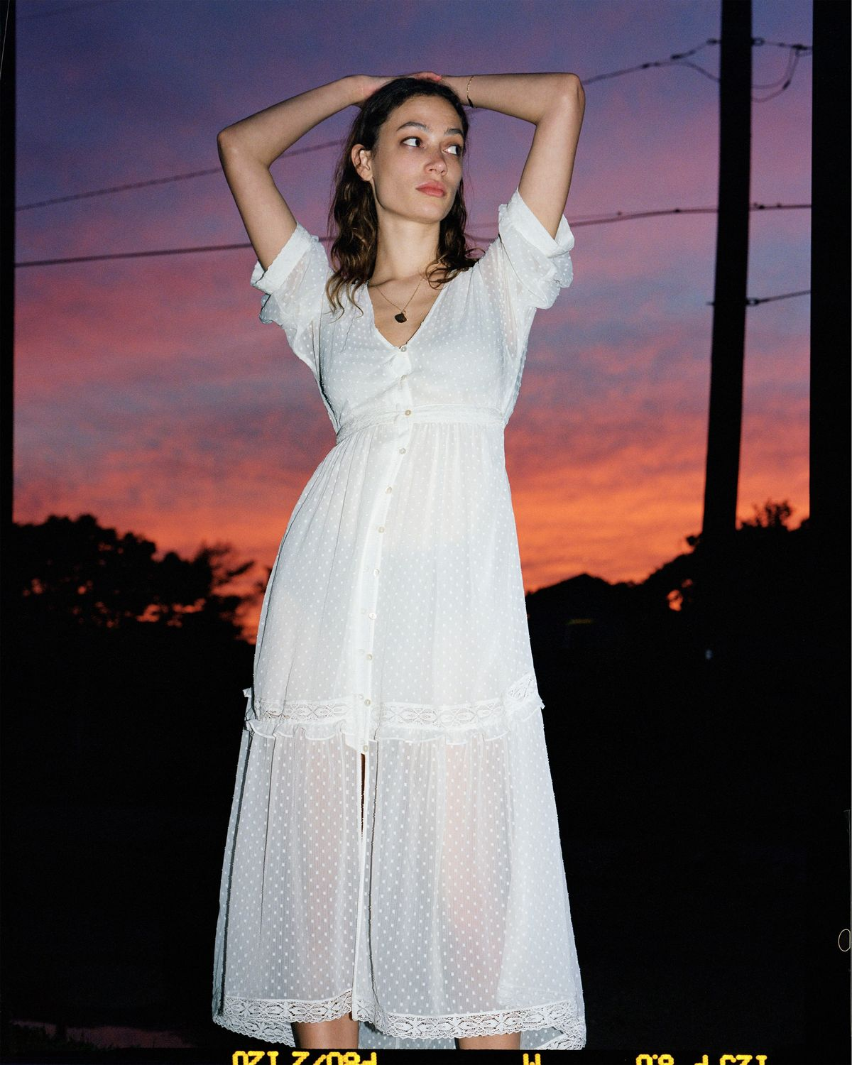 A photograph of a young woman posing in front of a vibrant sunset, wearing a long white dotted dress from our latest summer collection.