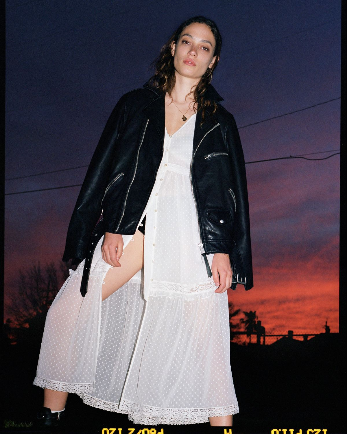 A photograph of a young woman posing in front of a vibrant sunset, wearing a long white dotted dress and a black leather jacket from our latest summer collection.