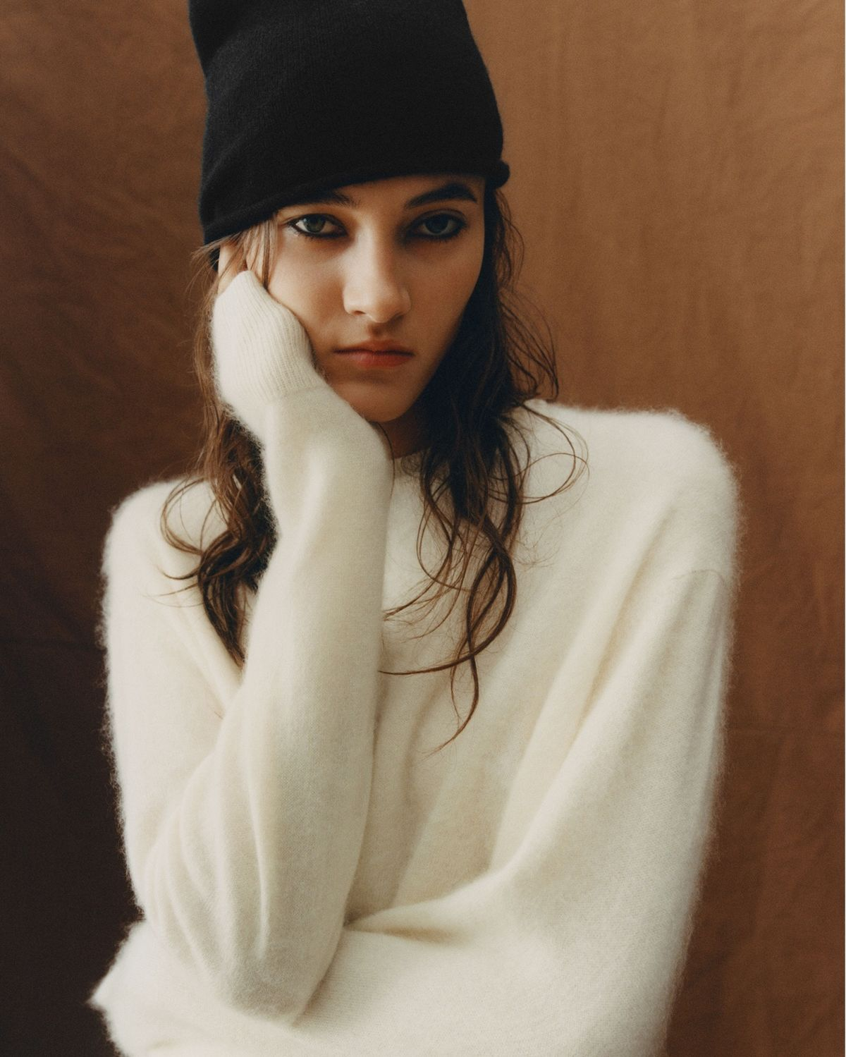 Portrait of a woman wearing a white jumper and black beanie.