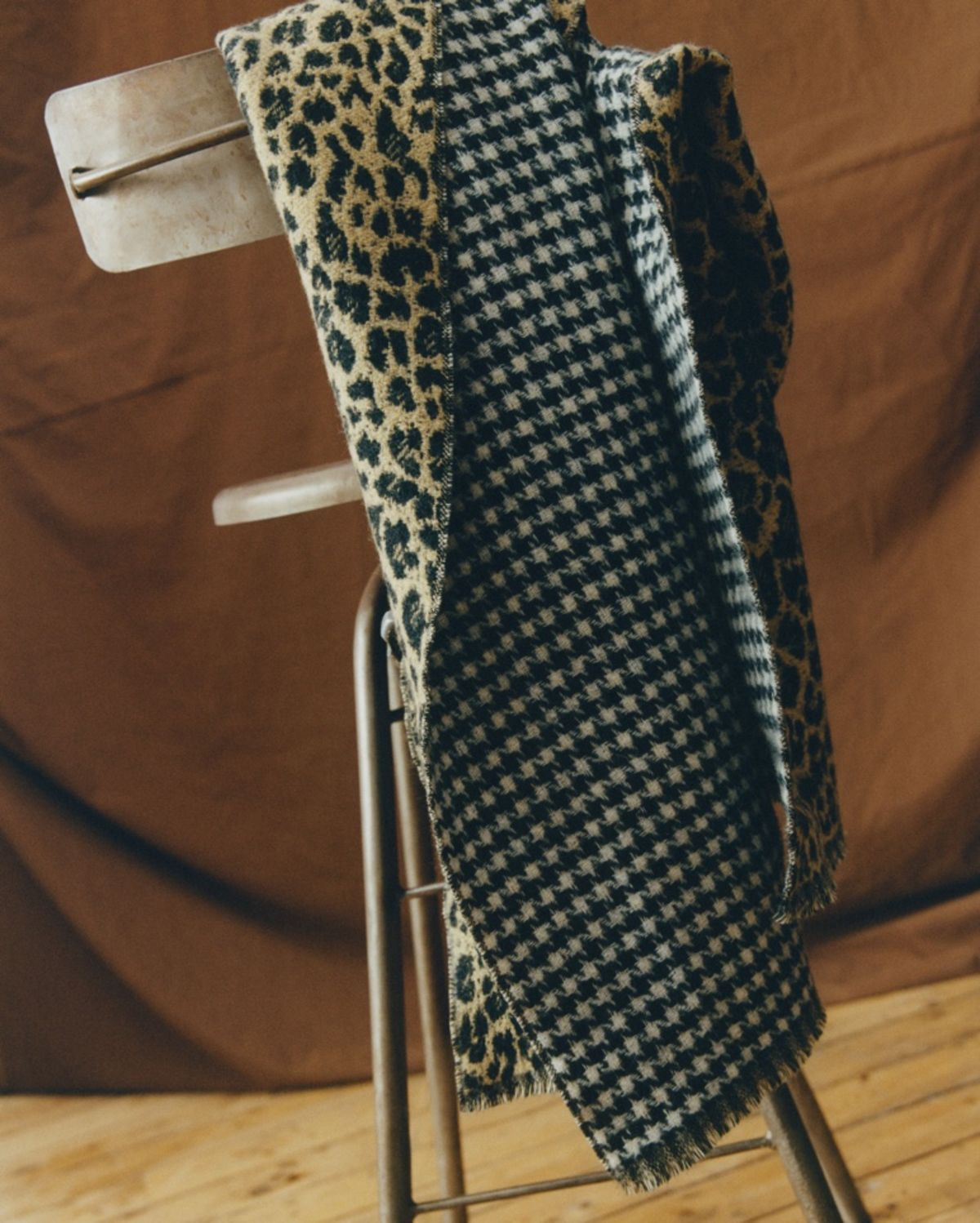 Shot taken in a studio of a reversible scarf resting on the back of a chair. One side of the scarf has a leopard pattern, the other side a black and white dogtooth pattern.