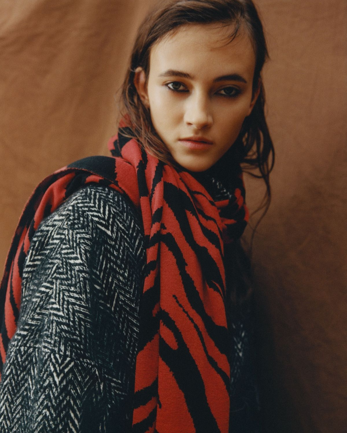 Portrait of a woman wearing a Herringbone coat with a red and black zebra scarf wrapped around her neck.