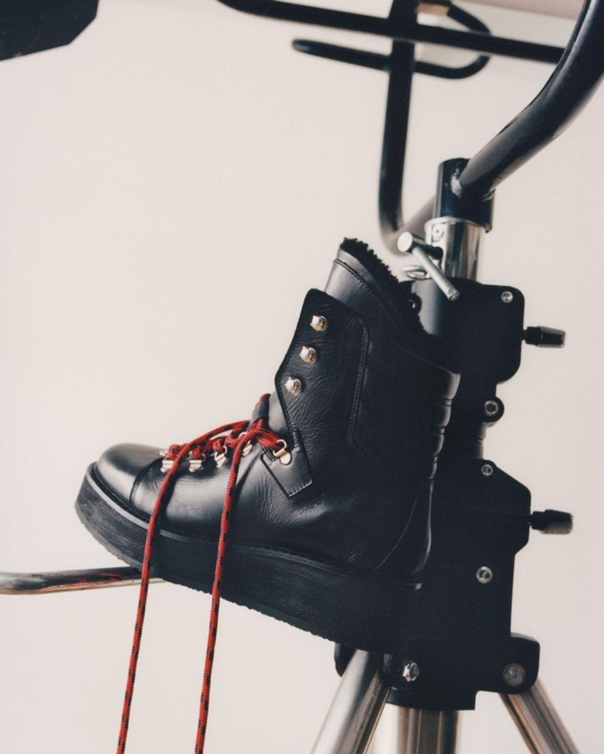 Shot taken in a studio of a pair of black leather boots with red laces and black fur on the inside.