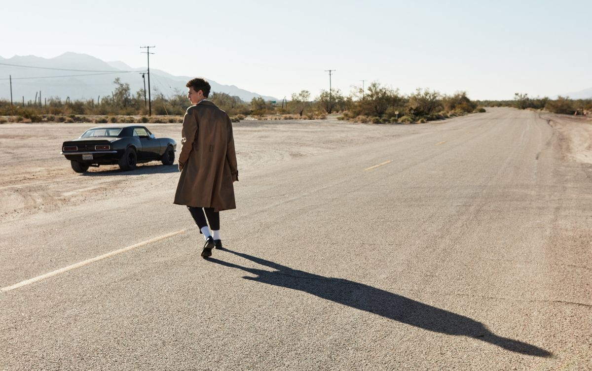 Image of a man walking on a desert road towards a black sports car wearing a camel trench coat with black tailored pants and black loafers.