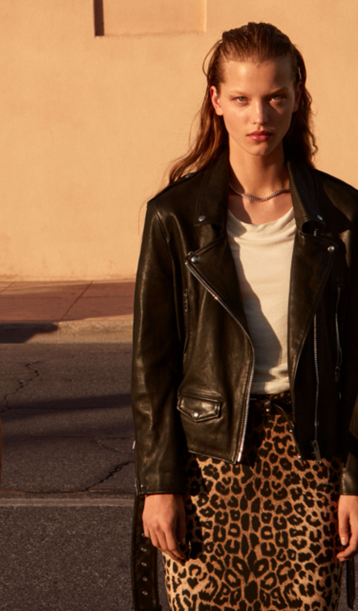 Woman wearing a leopard print skirt with a white t-shirt and black leather jacket.