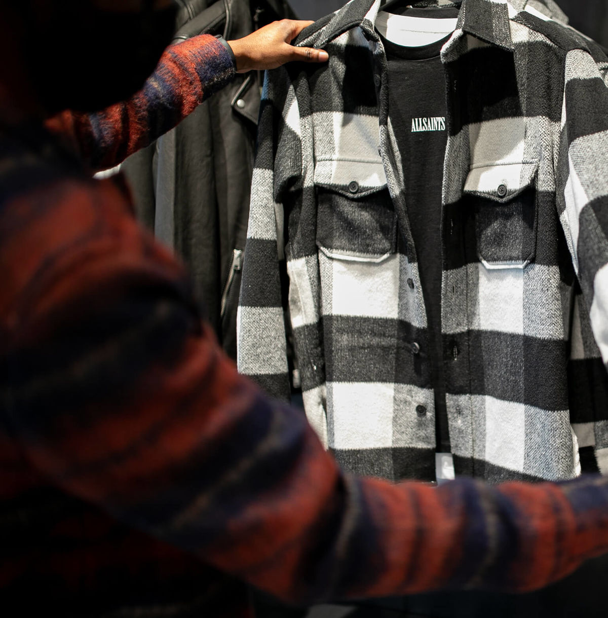 A member of our teams is holding a black and white checked shirt mechandised with a black t-shirt.
