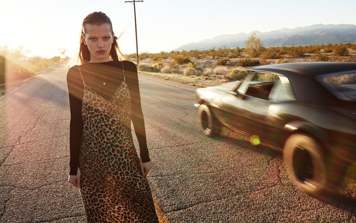 Woman standing on the road next to a driving sports car.