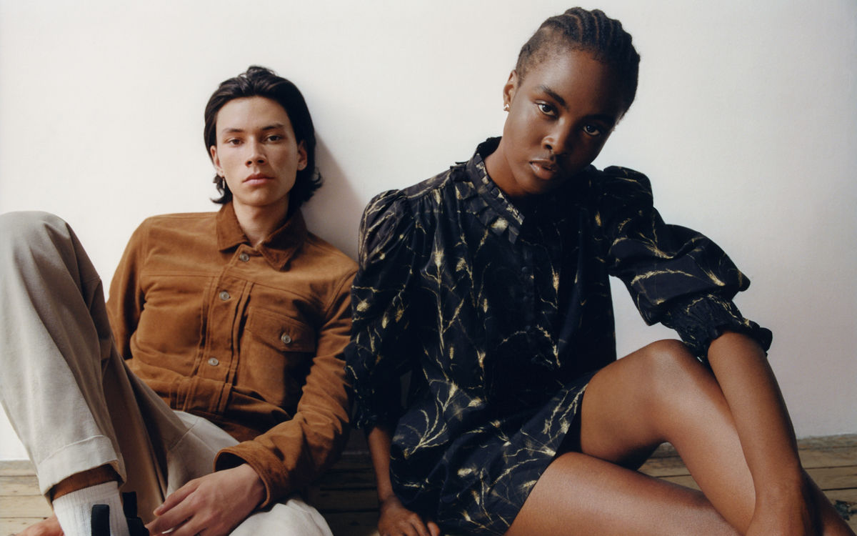 Man and a woman siting on the floor in front of a white wall wearing items from our new collection.