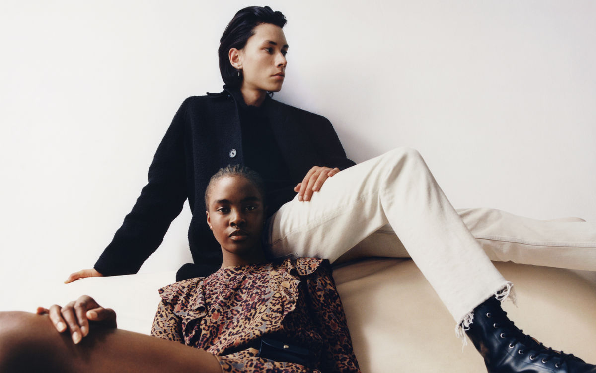 Woman and a man sitting on a couch wearing items from our latest collection.