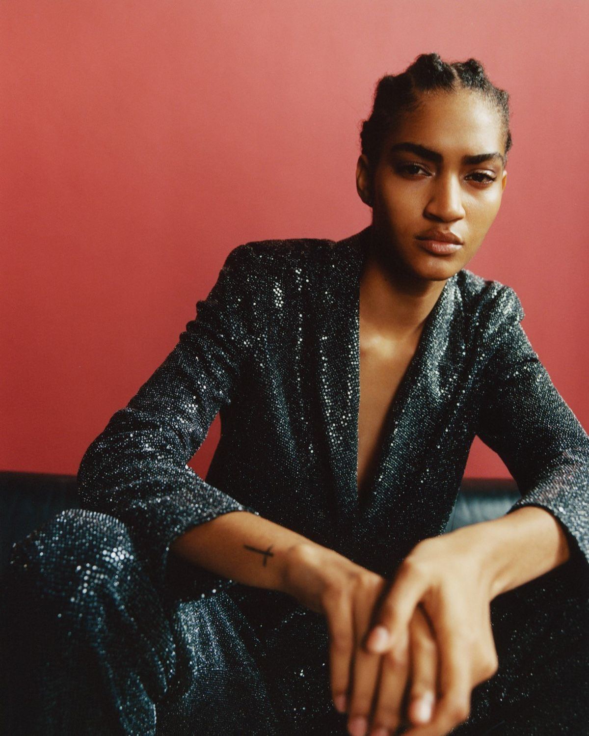 Picture of a girl seating on a black leather booth in front of a red wall wearing a sequined suit.