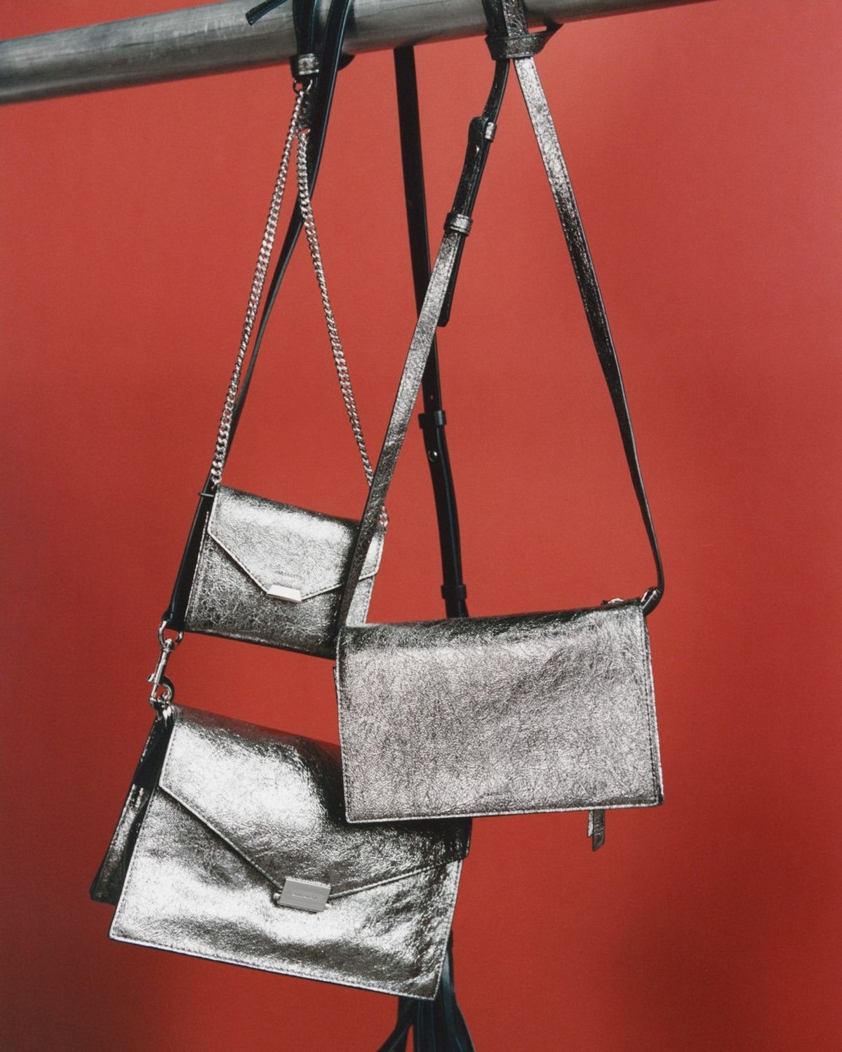 Image of three silver crossbody bags hanging in front of a red background.