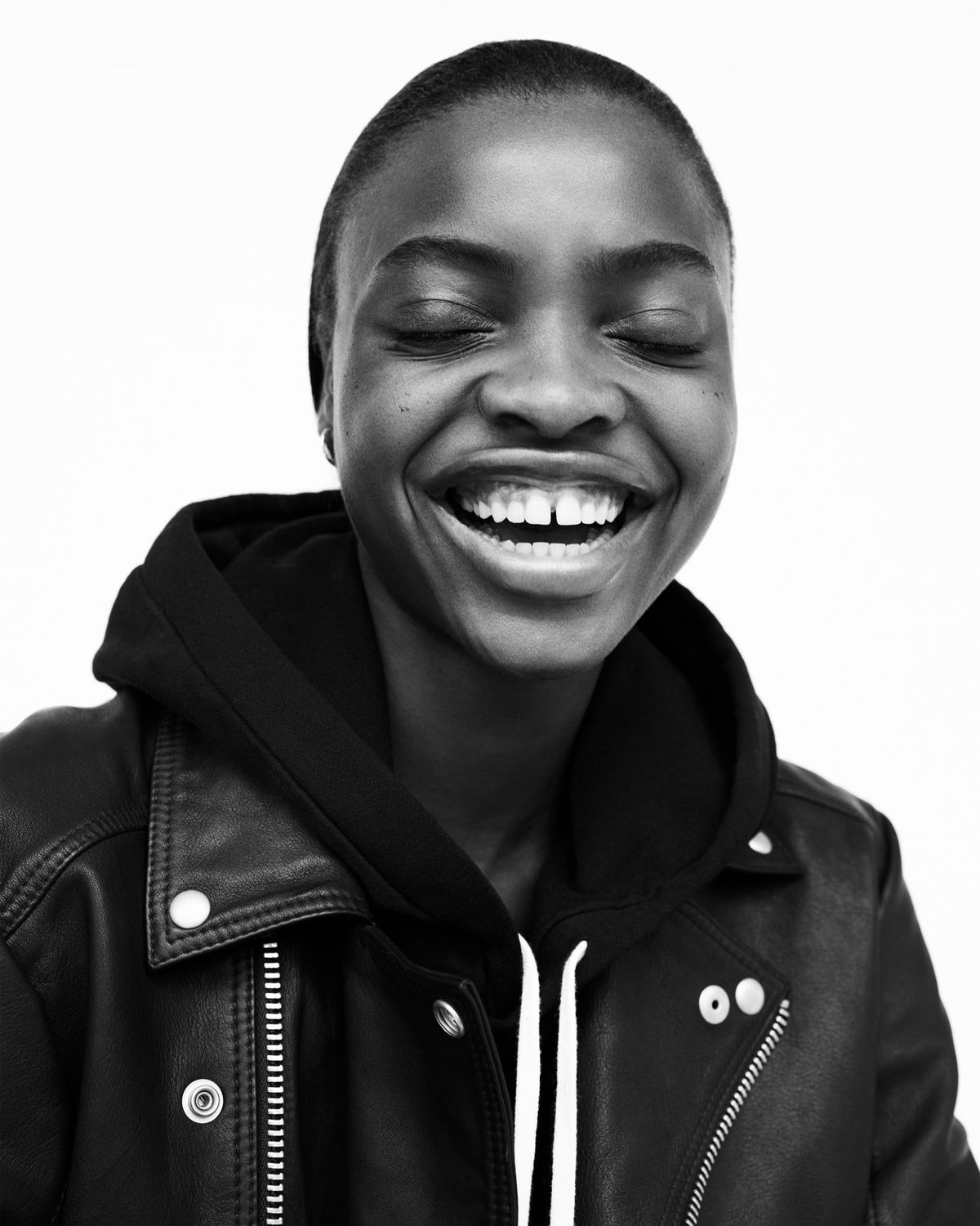 Black and white portrait of a woman smiling wearing a black hoodie under a black