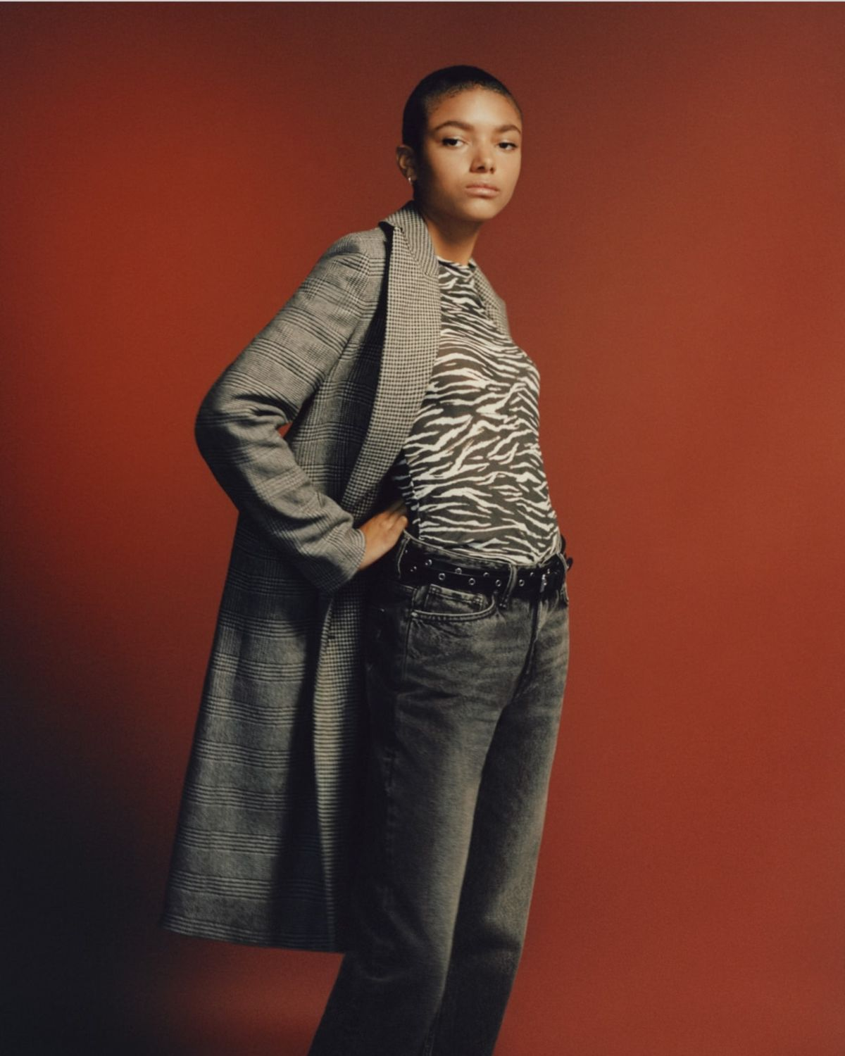 Image of a woman wearing a long checked coat over a zebra printed t-shirt and dark denim jeans.