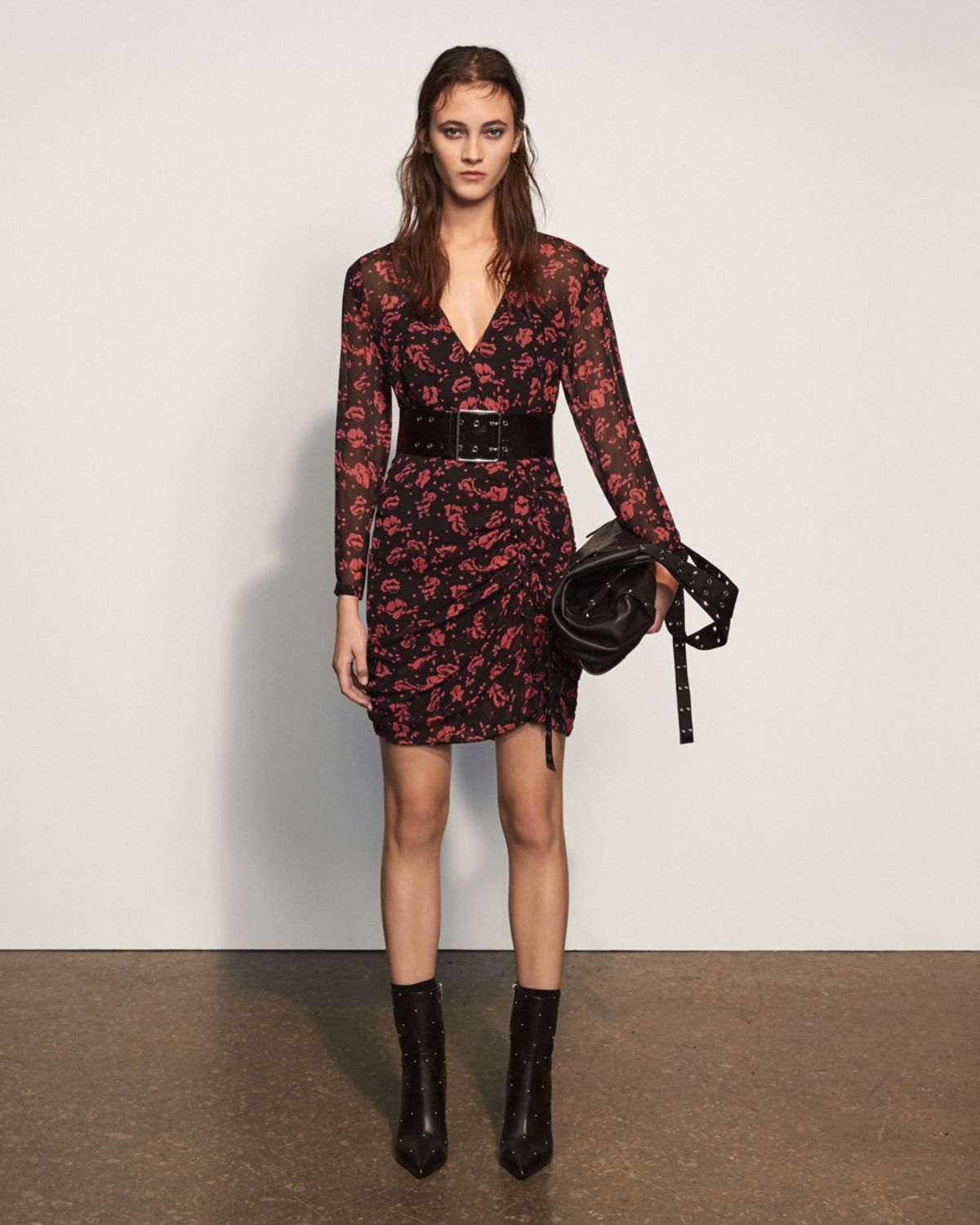 Image of a woman wearing a long sleeve floral printed dress styled with a black belt at the waist and black studded boots and bag.