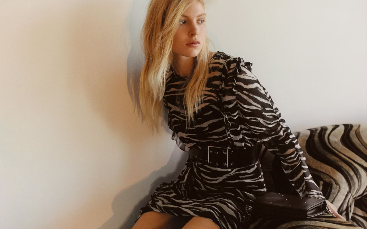 Image of a woman sitting on a couch and wearing a long sleeve zebra printed dress with a wide leather belt at the waist and a black studded clutch bag.