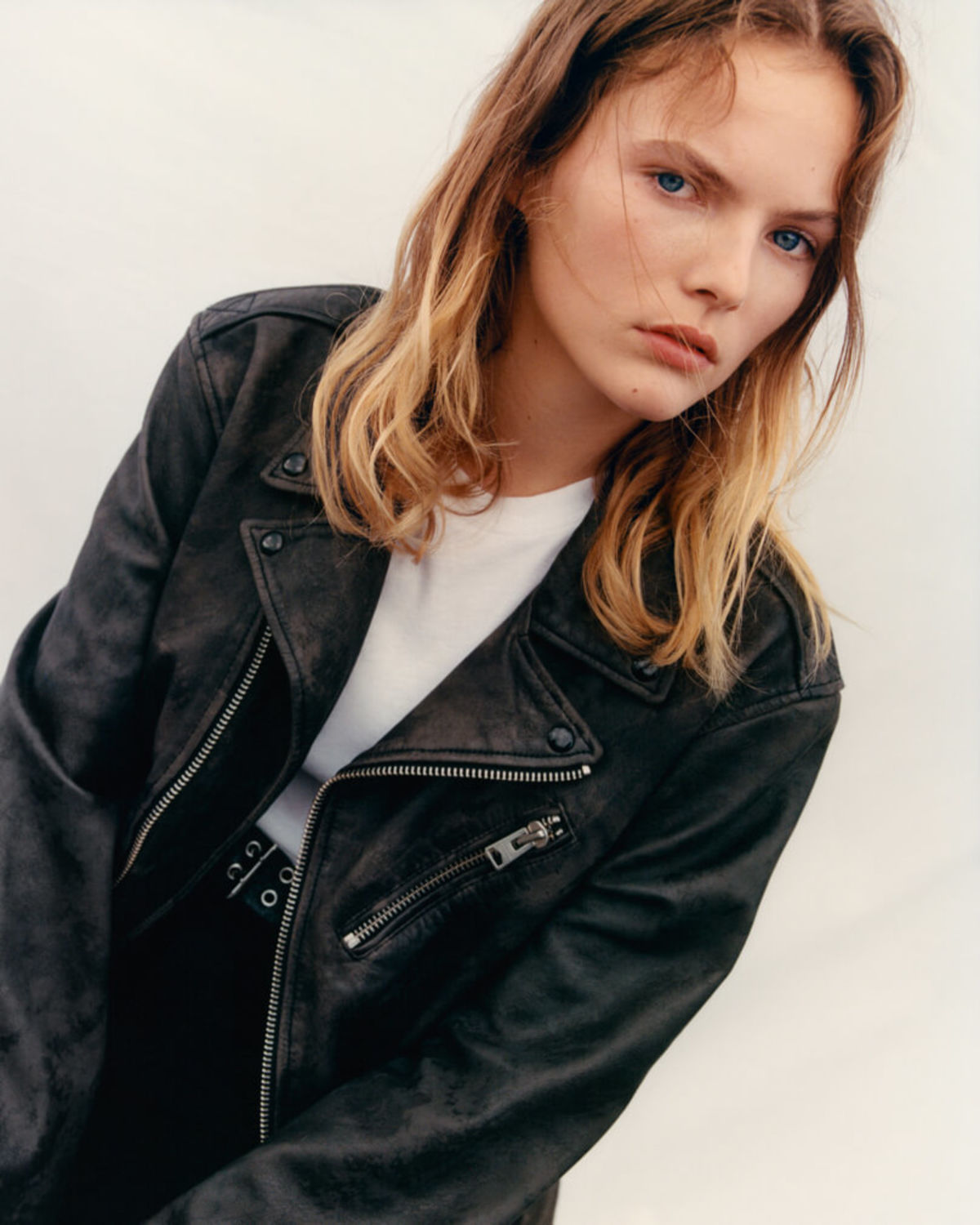 Portrait of a blonde woman wearing a black leather jacket over a white t-shirt.