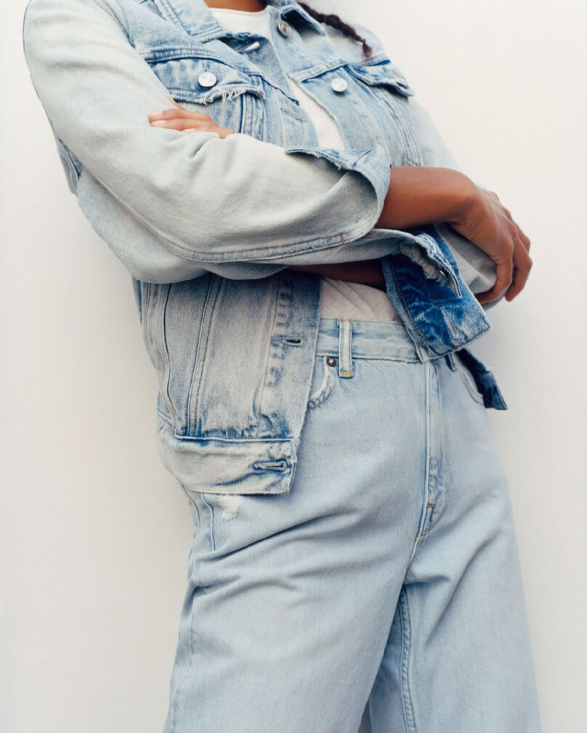 Cropped image of a woman wearing a light denim jacket with a white t-shirt and light denim jeans.