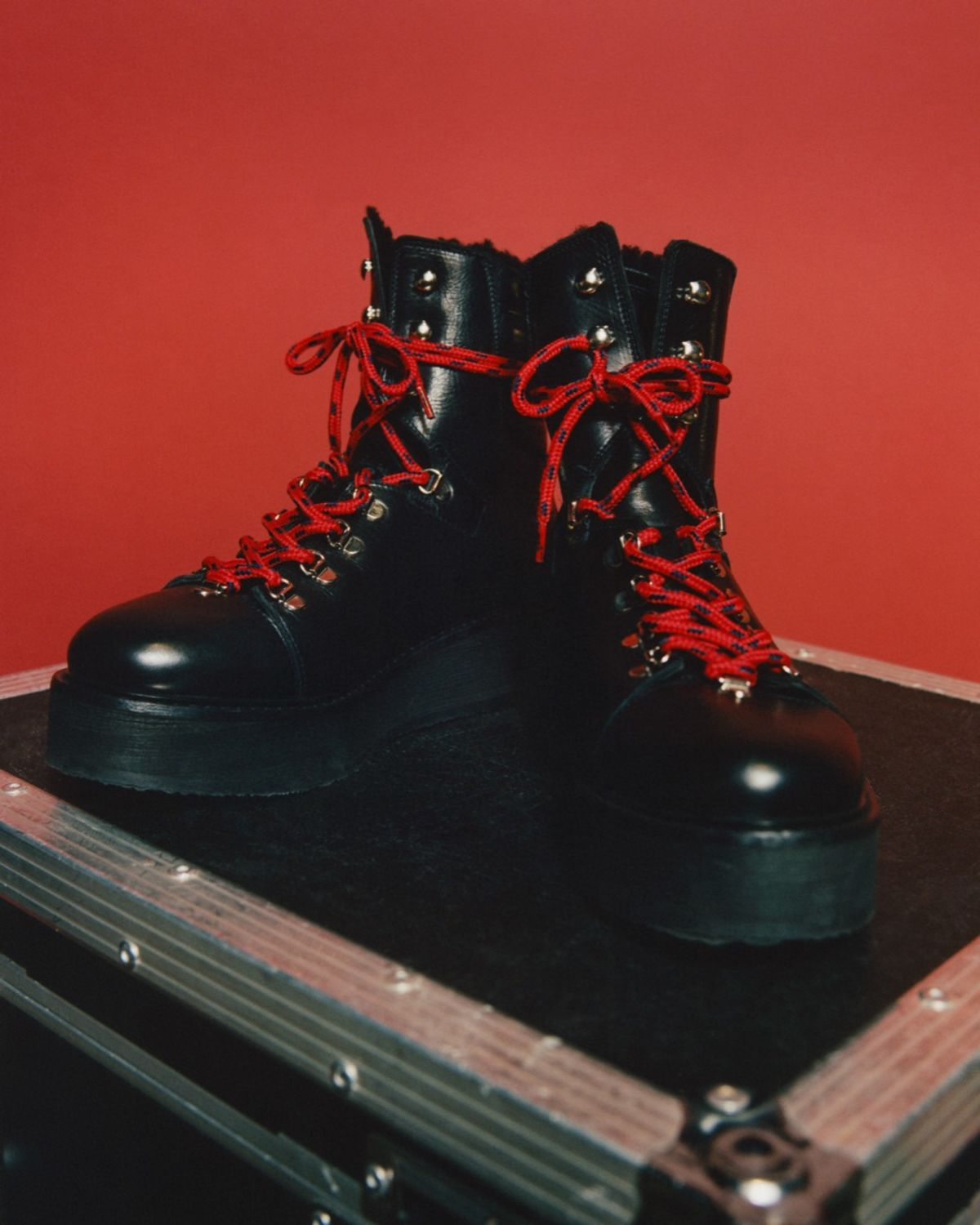 Close up of black leather military style shoes with red laces in front of a red background.