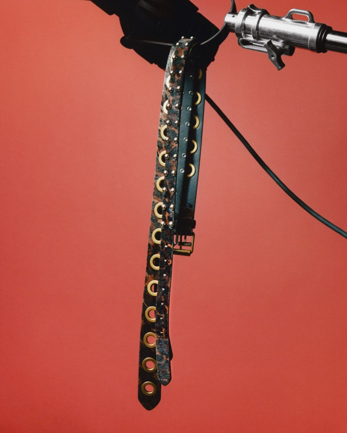 Close up of a few of our black and leopard printed leather belts hanging in front of a red background.