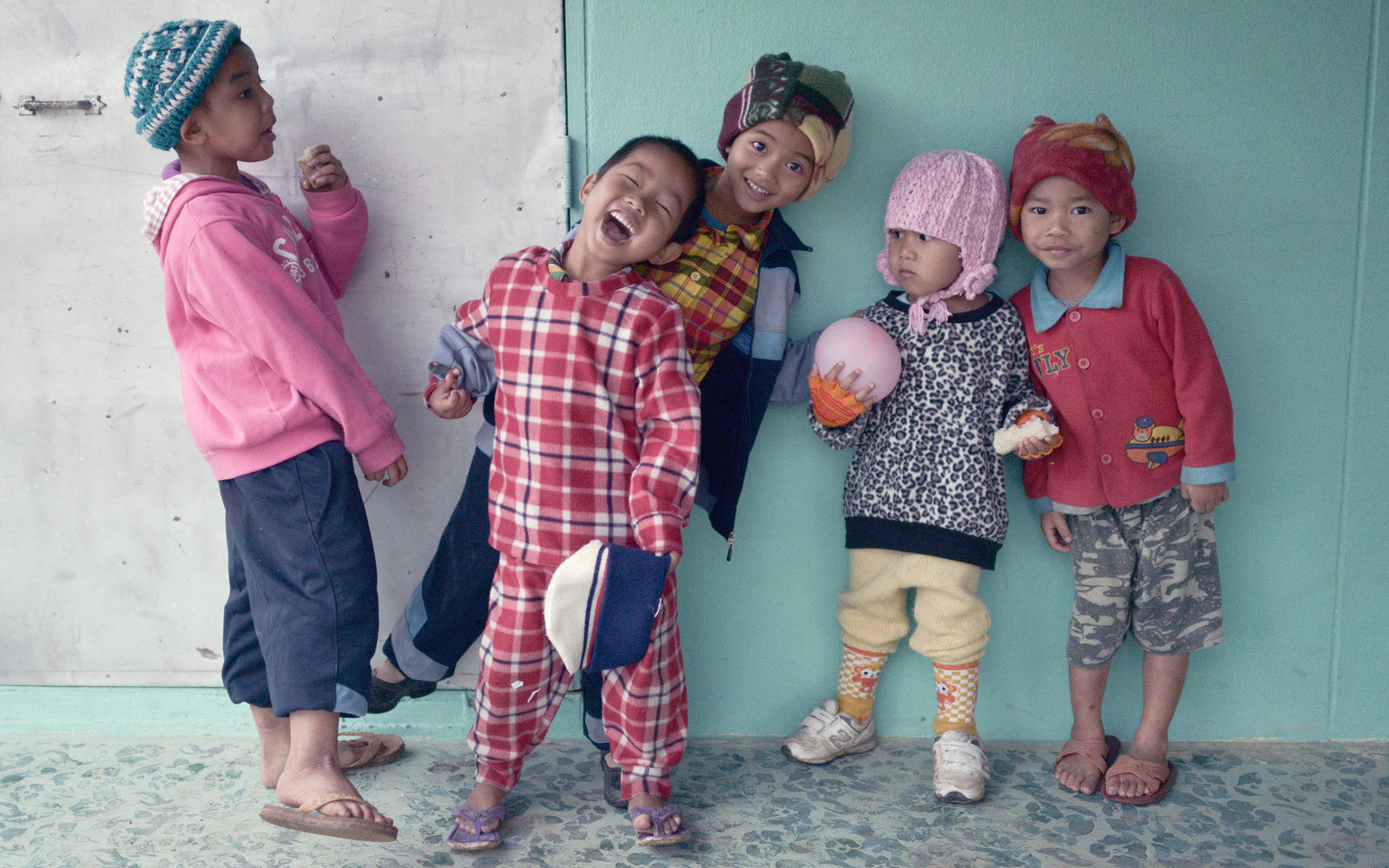 Photography of street kids posing and smiling, dressed in colourful mix-and-match clothes.