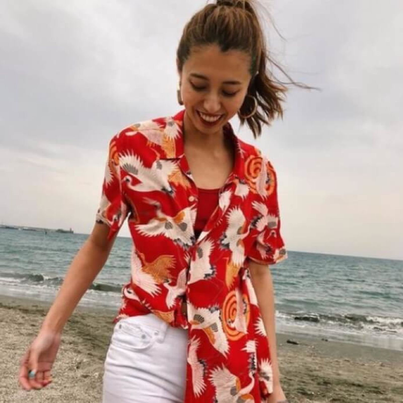Image of a woman wearing a red Hawaiian printed shirt with white jeans.