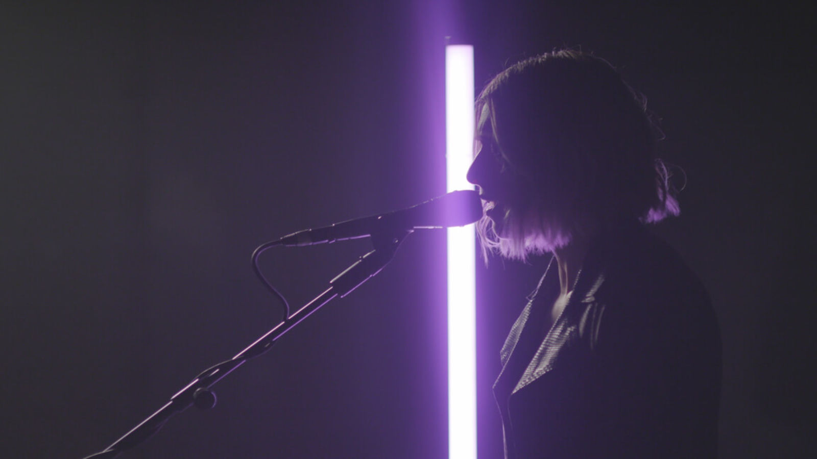Vérité singing close to her mic and standing before a neon light.