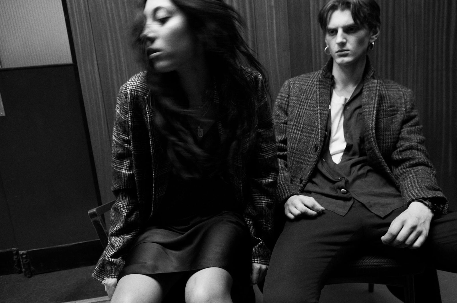 Black and white image of a woman and a man sitting in a corridor wearing items from our latest collection.