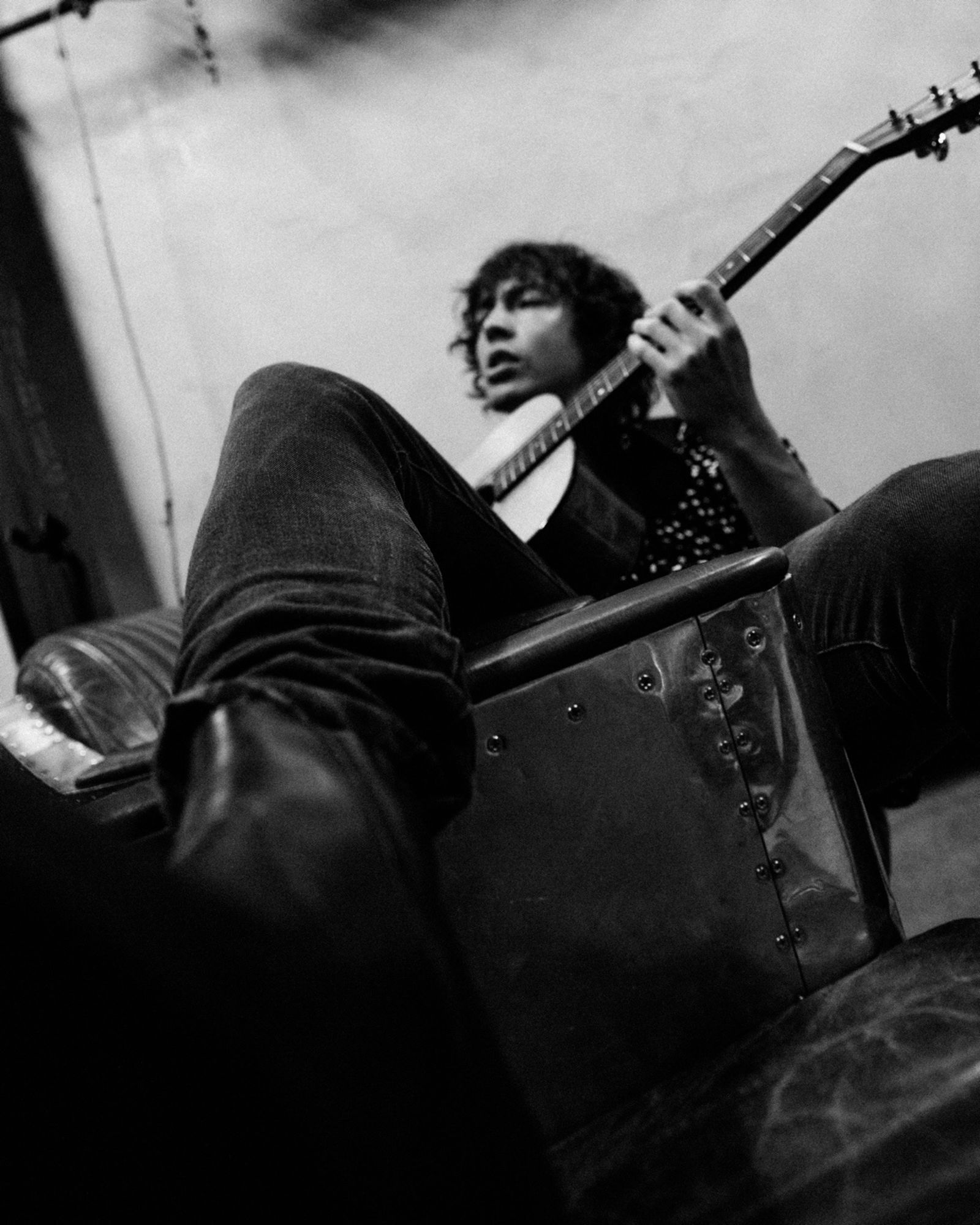 Black and white image of Barns Courtney sitting on a couch and playing on an accoustic guitar.