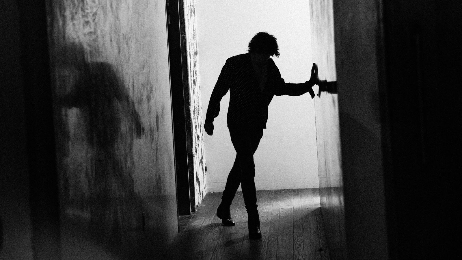 Black and white image of Barns Courtney walking in a corridor backstage.