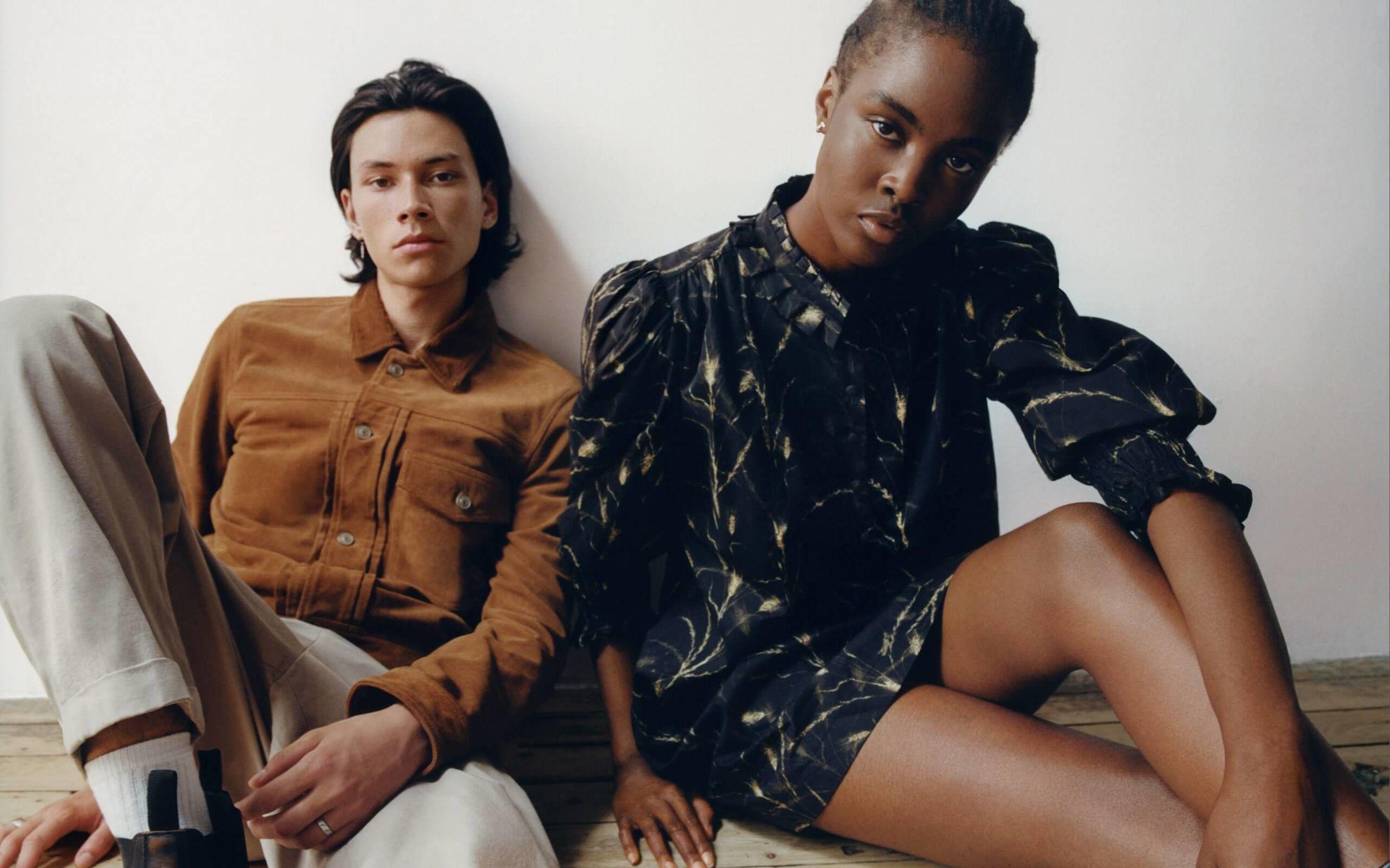 Eine Frau und ein Mann sitzen auf dem Boden an einer Wand und tragen Artikel aus unserer neuesten Kollektion.