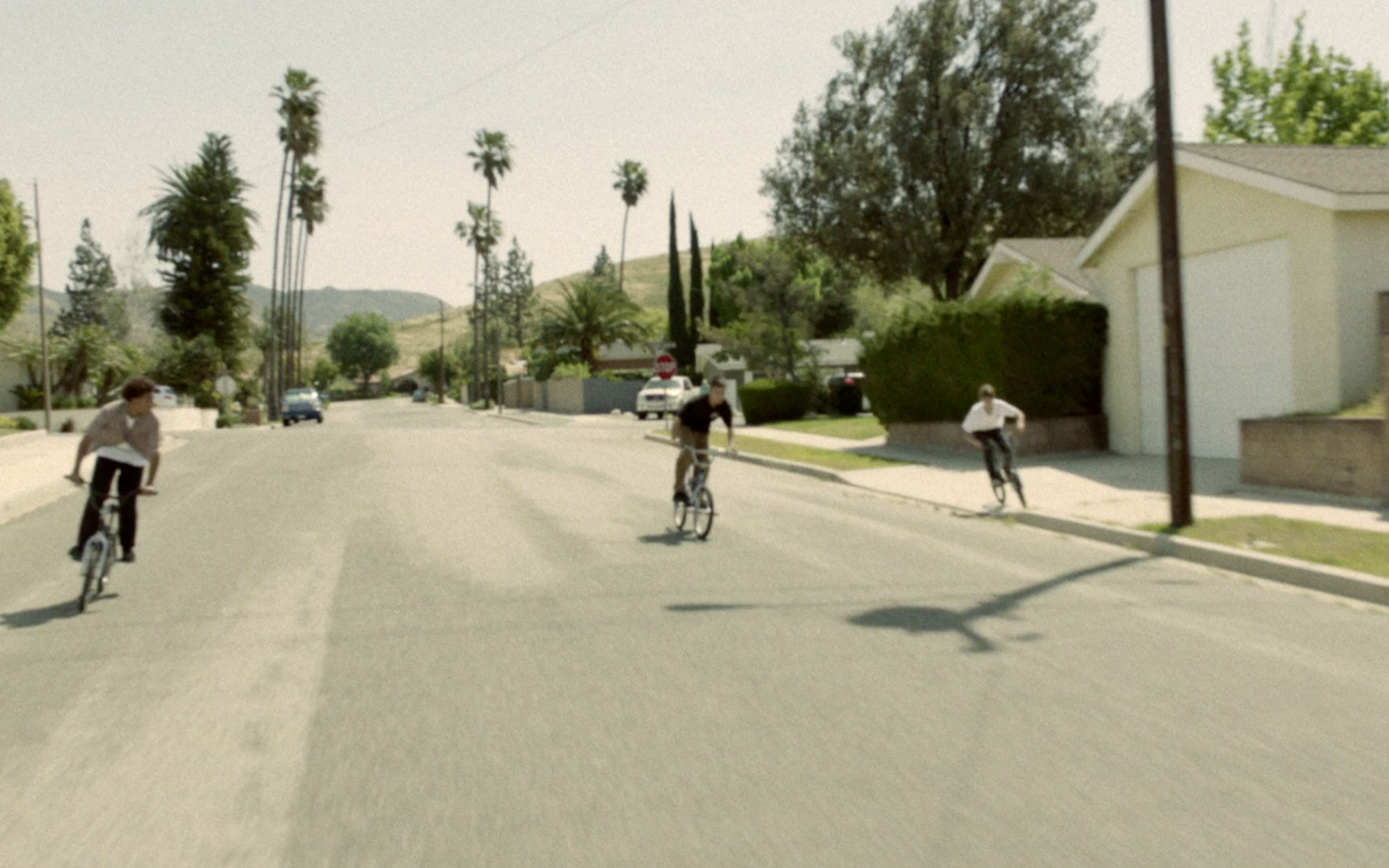 Video Thumbnail - Photo taken in a sunny street of LA of three kids on bikes wearing pieces from the new men's capsule collection