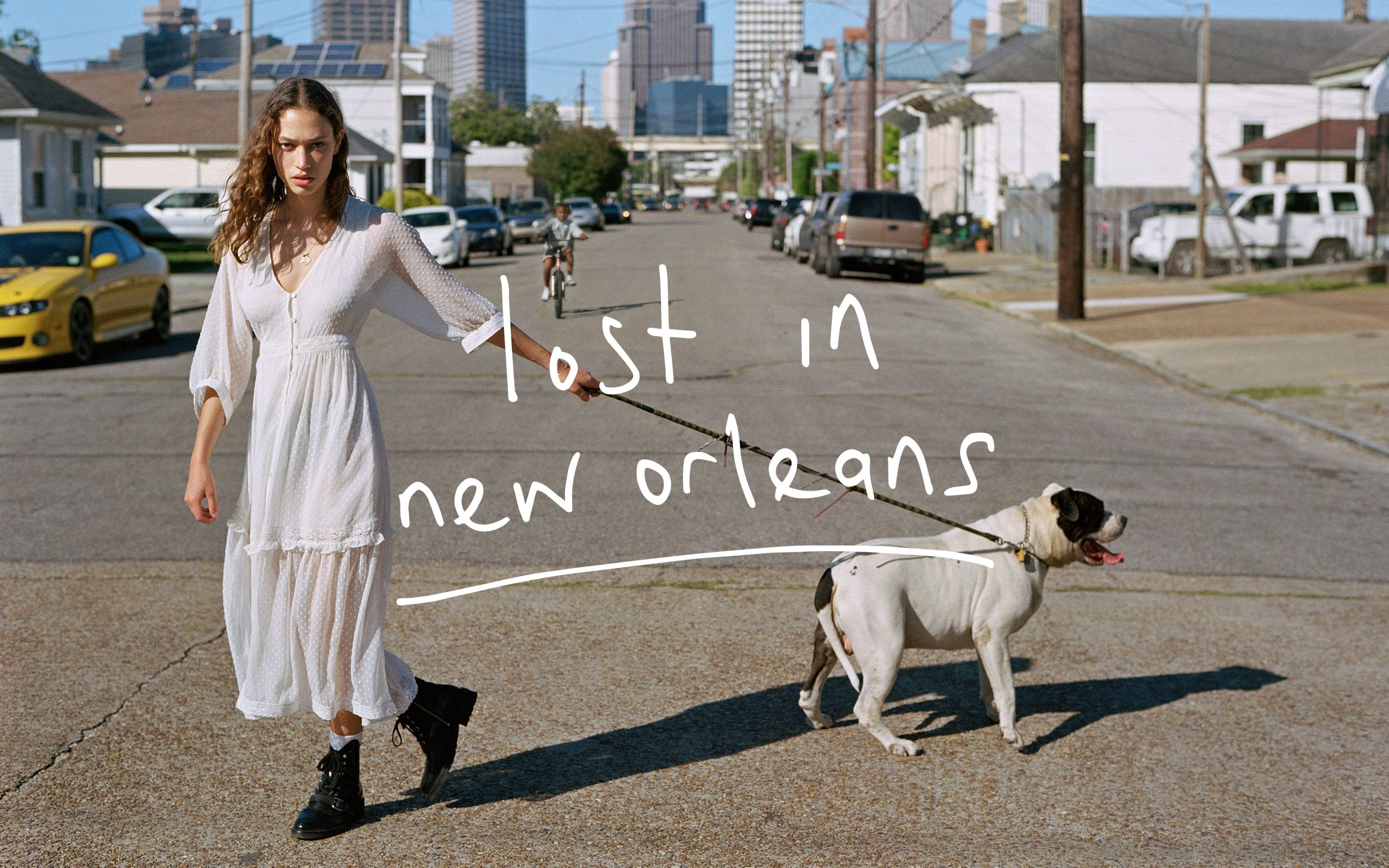 Landscape photograph shot in the streets of New Orleans featuring a woman walking a dog, wearing a long white dress from our latest summer collection.