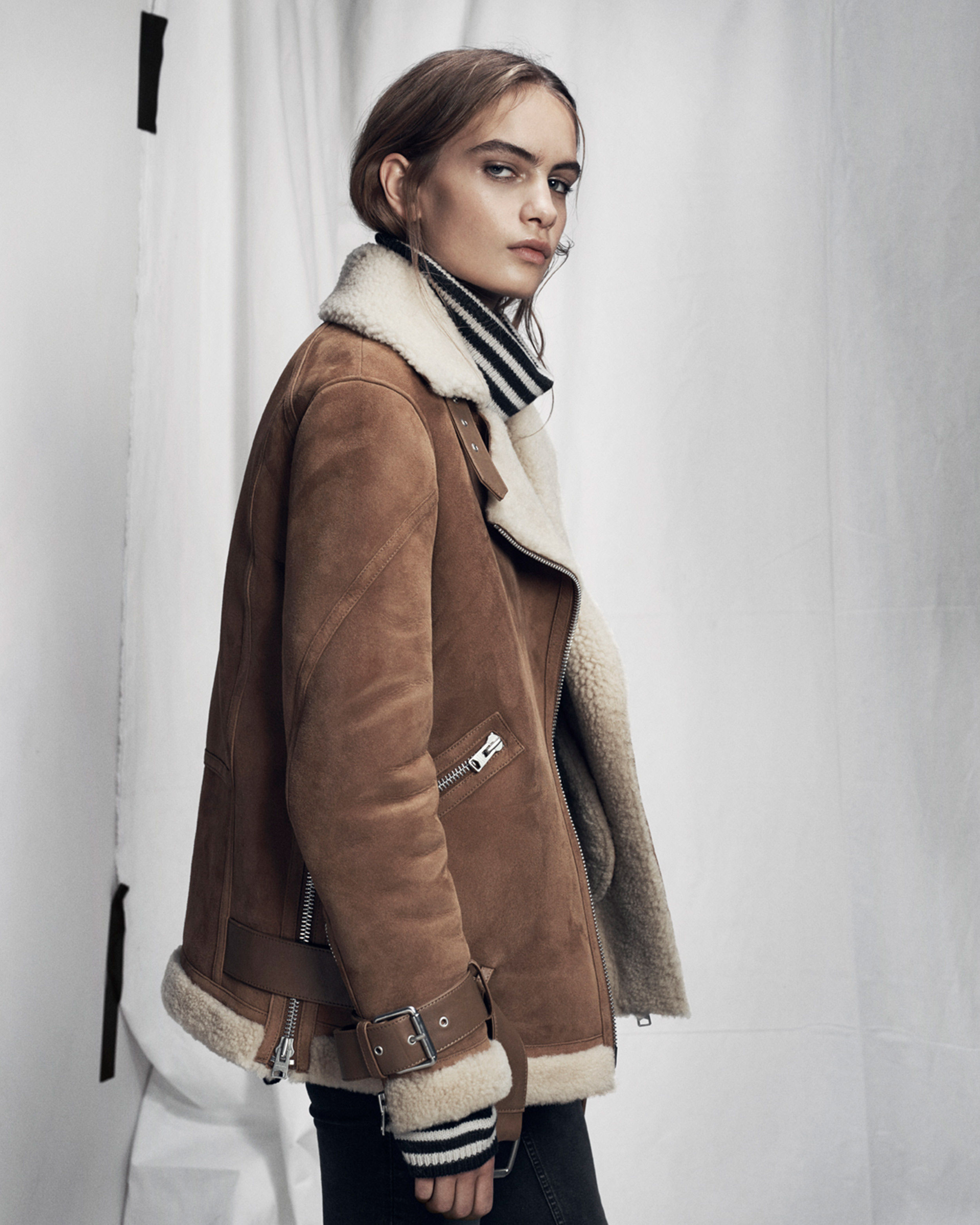 Lookbook image of a woman standing and wearing a brown shearling jacket over a funnel neck striped jumper.
