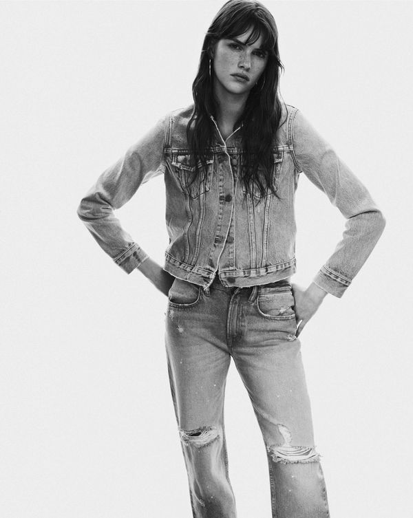 Women's Campaign Image in black and white, wearing a denim jeacket and jeans.