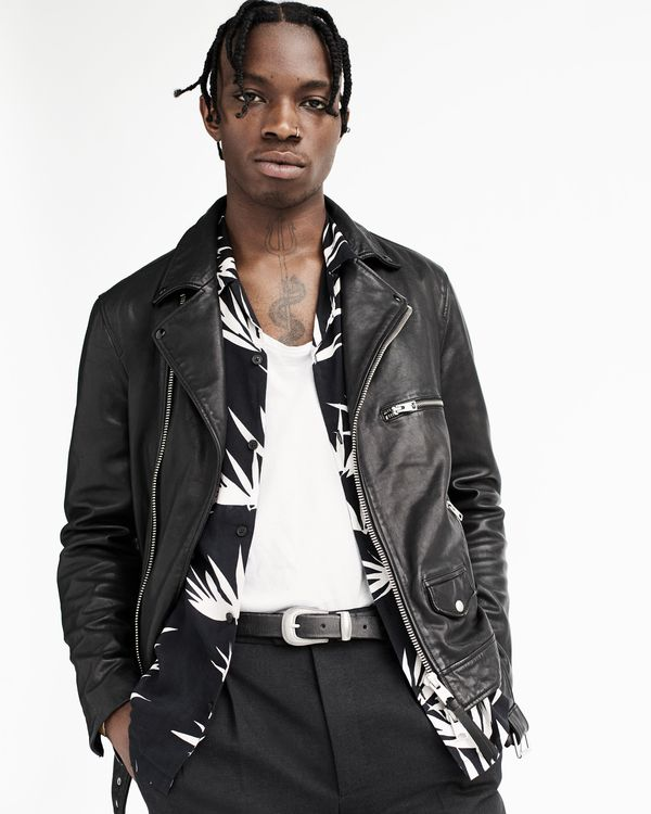 Portrait of a young man wearing a leather biker jacket and a printed shirt from our latest collection, layered over a white t-shirt and black tailored trousers.