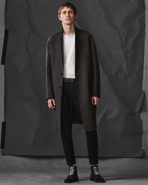 Lookbook image of a man wearing a long tailored grey coat from our latest collection, opened over a white t-shirt, with black jeans and military style boots.