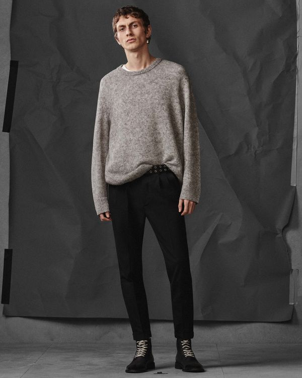 Lookbook image of a man wearing a light grey sweater with black jeans and military style boots.