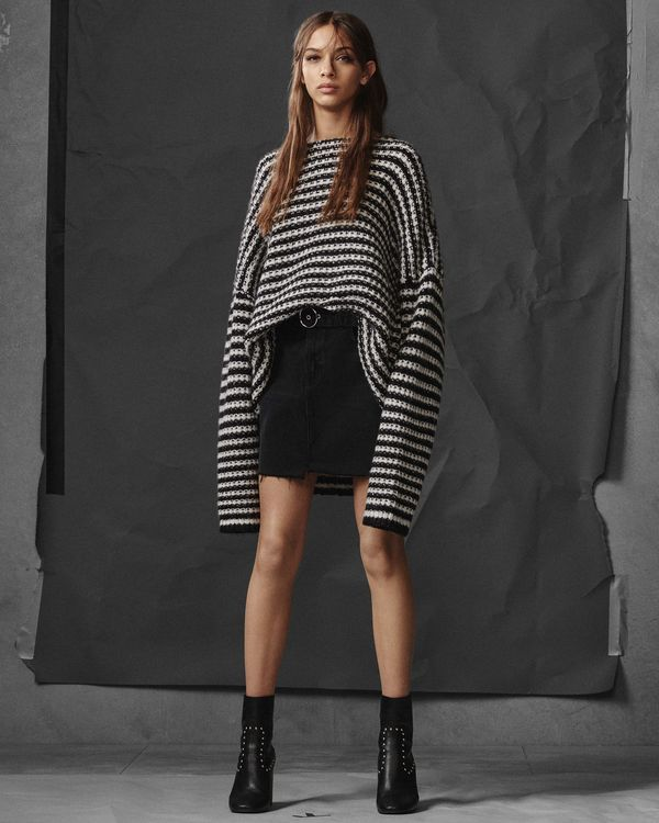 Lookbook image of a woman wearing an oversized striped sweater with a black skirt and high black studded boots.