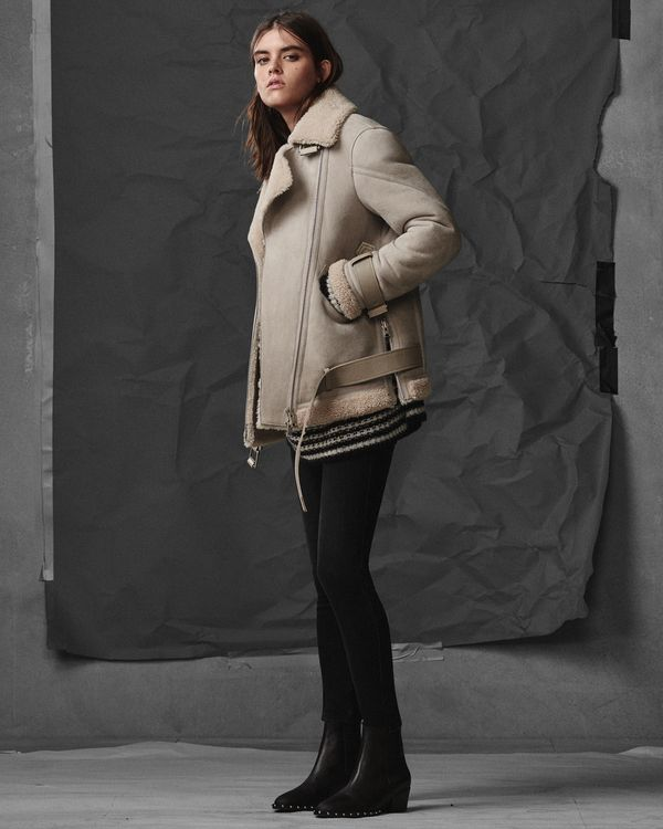 Lookbook image of a woman wearing an oversized beige shearling coat with black jeans and boots.