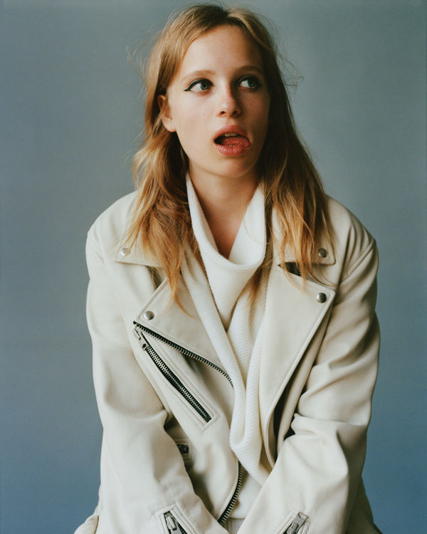Portrait of a woman wearing a knitted white dress underneath a white oversized leather jacket from our latest collection