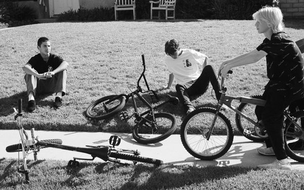 Black and white image of three boys hanging out with their bikes on a front garden and wearing our latest men's capsule collection