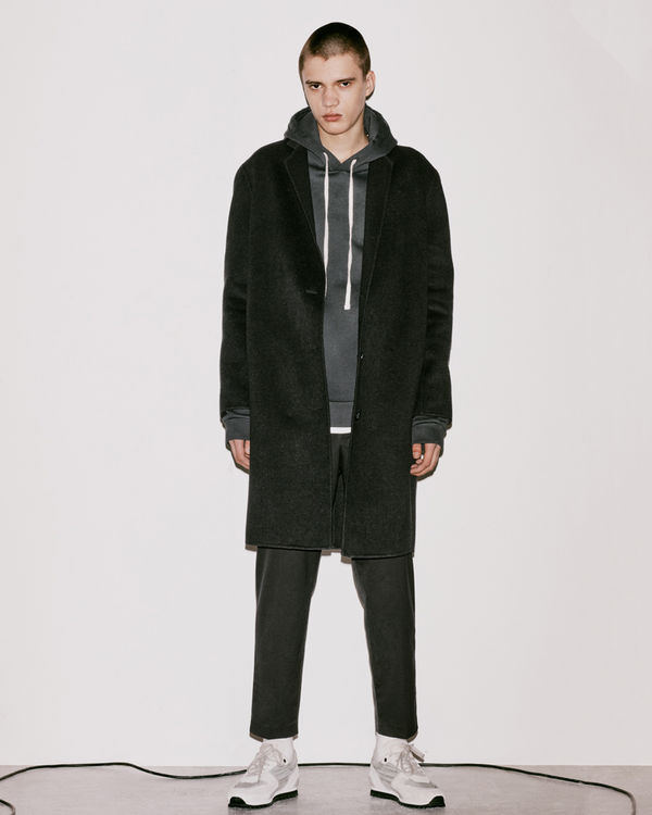 Lookbook image of a man wearing a coat from the latest collection.
