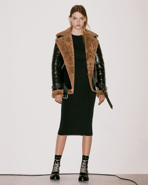 Lookbook image of a woman wearing an oversized shearling jacket over a knitted dress from the latest collection.