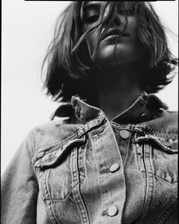 Black and white portrait photograph of a woman wearing a denim jacket from our latest collection.
