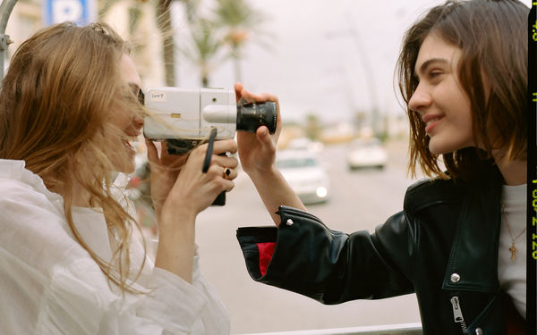 Campaign image of two women playing with a vintage video camera, wearing tops and leather jackets from our latest spring collection.