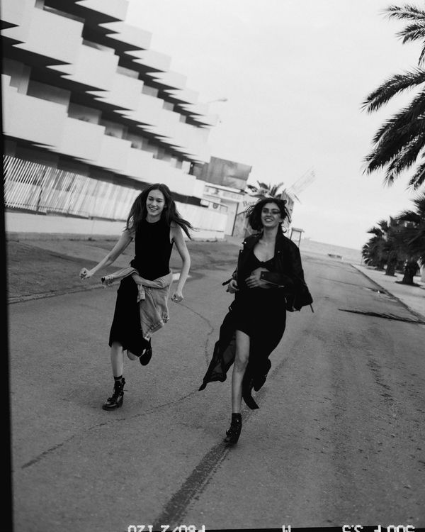 A black and white campaign image shot in the streets of Ibiza featuring two female models running, wearing our latest collection of leathers, dresses and boots.