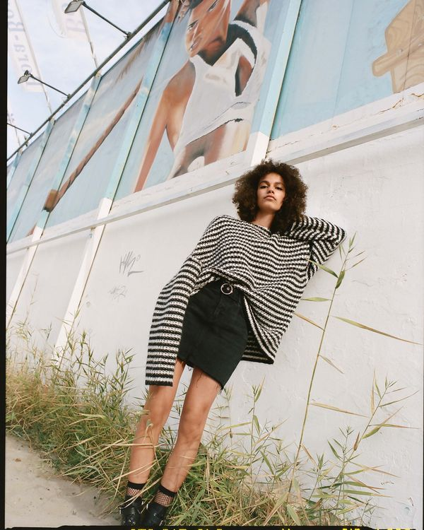 Campaign image of a woman leaning against a wall wearing an oversized knit paired with a black denim skirt.
